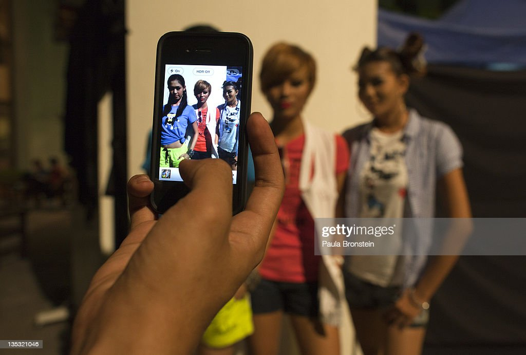 Jessica, 21, (L) and Thoori ,19, pose showing off their clothing as a friend takes iPhone photos backstage during a show featuring OPT jeans December 8, 2011 in Yangon, Myanmar. Very few Burmese can afford to have a mobile phone which can cost over 600 US just for the sim card and service. The handsets are also much higher price than other countries as telecommunications struggles to catch up with the rest of the world. The pace of change in Myanmar brought U.S Secretary of State Hillary Clinton to the country where she discussed further paths to reform and crucial talks with both Aung San Suu Kyi and the highest levels of the Burmese government. For many years Myanmar has suffered from economic stagnation, political repression and international isolation. In March the army handed power to a civilian government after almost five decades of the military regime's strong arm rule. The handover took place after a controlled election under a new constitution that preserved much of the military clout. Internet has been loosened up as previously inaccessible foreign news and opposition websites have been unblocked.