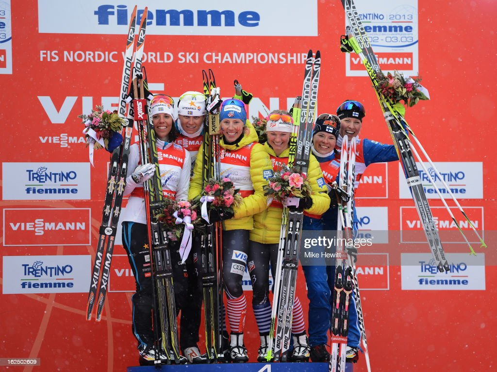 Jessica Diggins and Kikkan Randall of the United States celebrate victory on the podium with second placed Ida Ingemarsdotter and Charlotte Kalla of Sweden and third placed Riikka Sarasoja-Lilja and Krista Lahteenmaki of Finland following the Women's Team Sprint Final at the FIS Nordic World Ski Championships on February 24, 2013 in Val di Fiemme, Italy.