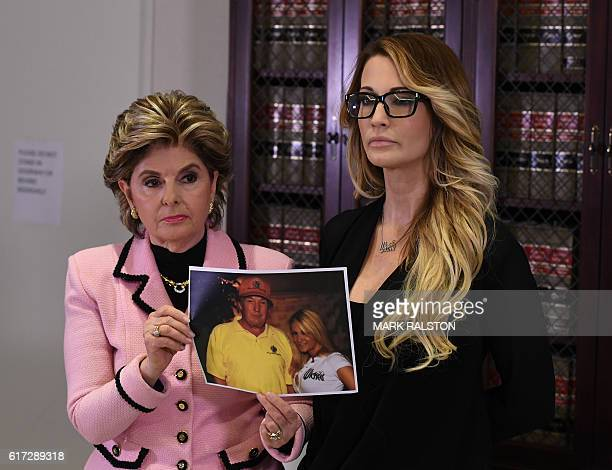 jessica drake who works for an adult film company stands with a photo of her meeting with Donald Trump beside attorney Gloria Allred as they talk...