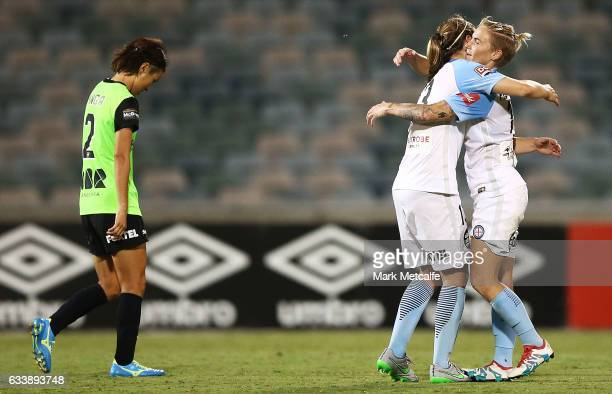 Jessica Fishlock and Rebekah Stott of Melbourne City celebrate victory as Yukari Kinga of Canberra looks dejected after defeat at the end of the...
