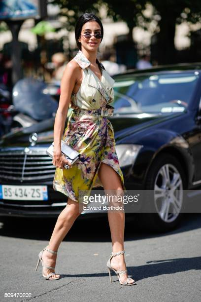 Jessica Kahawaty wears sunglasses a flower print dress and a silver bag outside the Jean Paul Gaultier show during Paris Fashion Week Haute Couture...