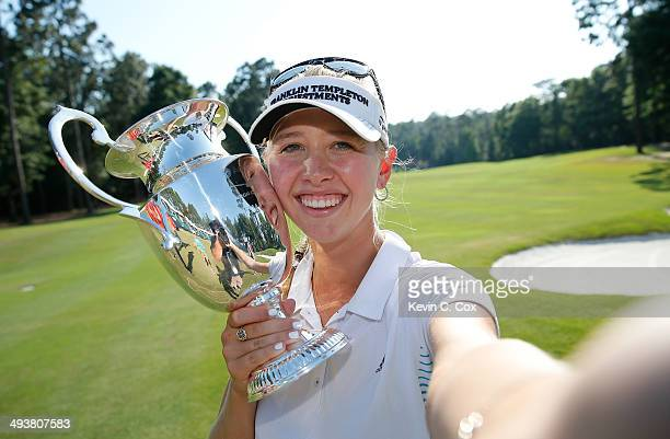 Jessica Korda pretends to take a selfie while holding the trophy on the 18th green after winning the Airbus LPGA Classic presented by JTBC at the...