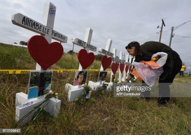 Jessica Mires leaves flowers on crosses named for the victims outside the First Baptist Church which was the scene of the mass shooting that killed...