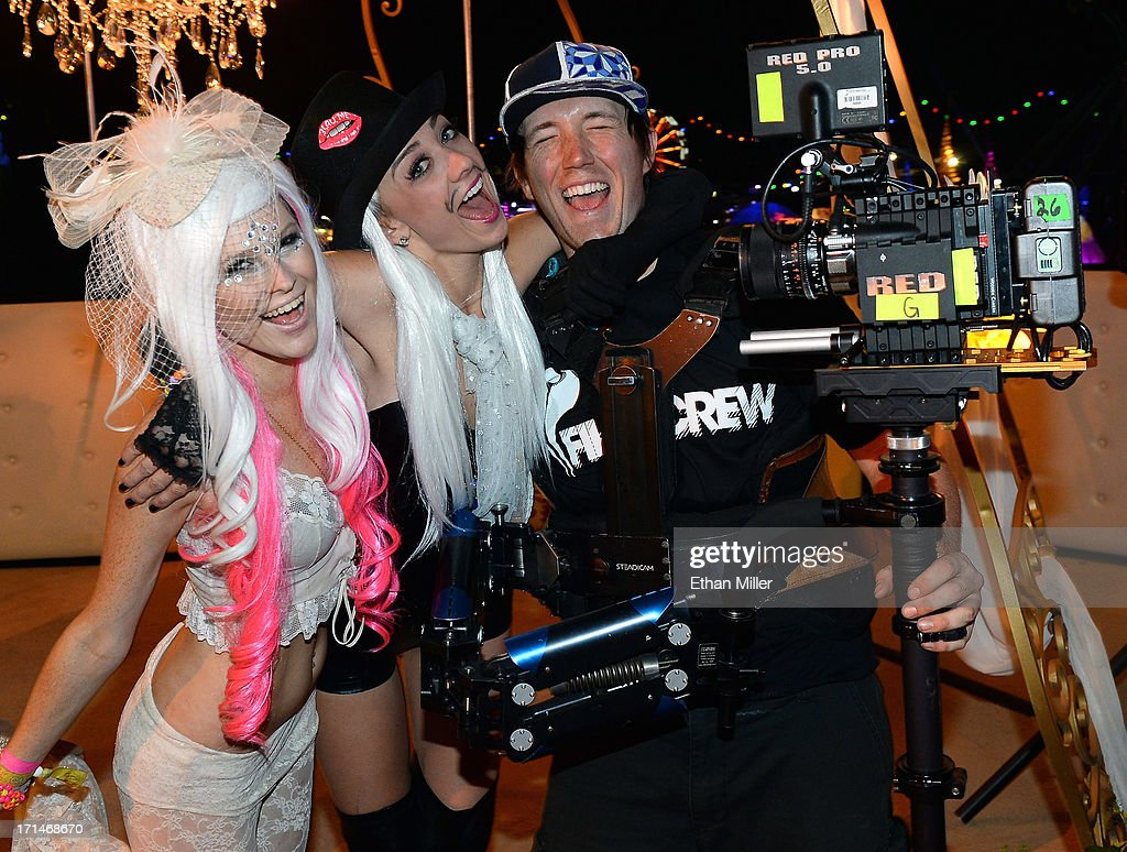 Jessica O'Donnell and Adele Vannini pose with EDC film crew member William Walsh after he filmed the women's commitment ceremony at the 17th annual Electric Daisy Carnival at Las Vegas Motor Speedway on June 23, 2013 in Las Vegas, Nevada.
