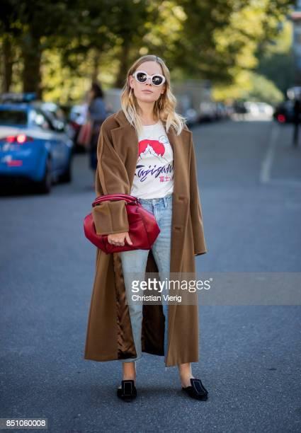 Jessie Bush wearing brown coat denim jeans red bag is seen outside Max Mara during Milan Fashion Week Spring/Summer 2018 on September 21 2017 in...
