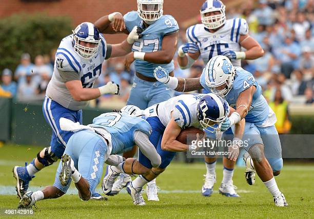 Jessie Rogers and Sam Smiley of the North Carolina Tar Heels tackle quarterback Thomas Sirk of the Duke Blue Devils on a quarterback draw during...
