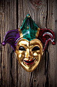 Jester mask hanging on wooden wall
