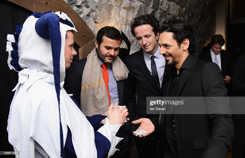 A jester performs a magic trick with actor and friend of the Roger Dubuis brand, Tomer Sisley (R) at the Excalibur Dinner during the 23rd Salon International de la Haute Horlogerie at Caves des Vollandes on January 23, 2013 in Geneva, Switzerland.