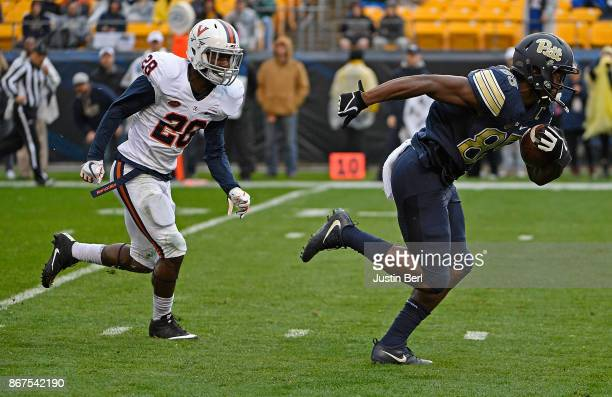 Jester Weah of the Pittsburgh Panthers runs up field past Brenton Nelson of the Virginia Cavaliers after a catch for a 19 yard touchdown reception in...