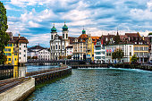 Beautiful Cityscape of old town Lucerne, visible are Jesuit Church, the river Reuss waterfront of Lucerne with the famous Kapellbrucke bridge built in 1333, traditional swiss buildings, restaurants, c