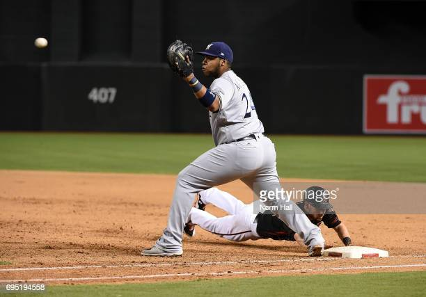 Jesus Aguilar of the Milwaukee Brewers covers first base while waiting for a throw from the pitchers mound as Chris Owings of the Arizona...