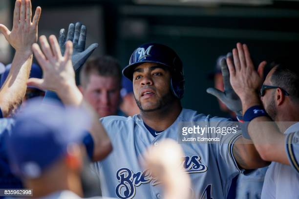 Jesus Aguilar of the Milwaukee Brewers is congratulated in the dugout after hitting a solo home run during the second inning during the game against...