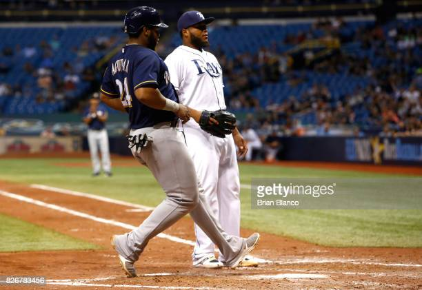 Jesus Aguilar of the Milwaukee Brewers runs in to score in front of pitcher Jose Alvarado of the Tampa Bay Rays off of the wild pitch by Alvarado...