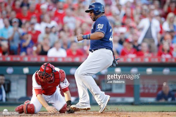 Jesus Aguilar of the Milwaukee Brewers scores after the ball was dropped by Devin Mesoraco of the Cincinnati Reds in the third inning of a game at...