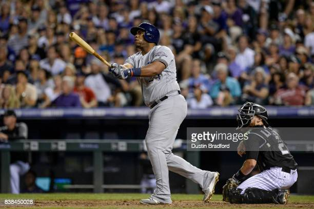 Jesus Aguilar of the Milwaukee Brewers watches the flight of a ninth inning two run homerun hit off of Greg Holland of the Colorado Rockies at Coors...