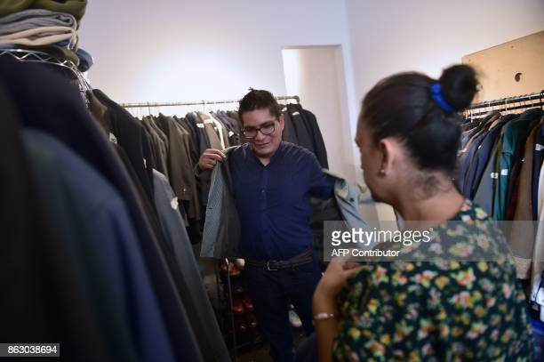 Jesus Dominguez tries a blazer on at a 'boutique' that gives away donated crisp business clothes to those who on Mexico's September 19 quake lost...
