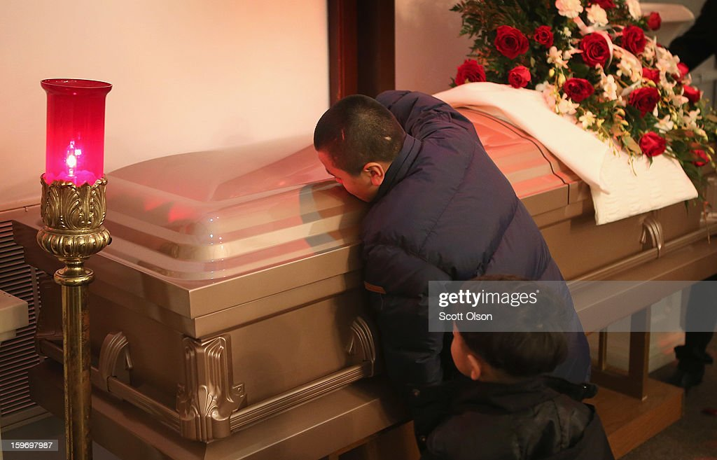 Jesus Dorantes, 11, kisses the casket of his brother Rey Dorantes during his wake on January 17, 2013 in Chicago, Illinois. Rey Dorantes, 14, died after being shot six times while he was sitting on the front porch of his home on January 11. Dorantes's murder was the 21st homicide recorded in Chicago for 2013, a city which saw more than 500 homicides in 2012.