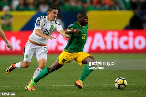 Jesus Dueñas of Mexico and Michael Binns of Jamaica compete for the ball during a Group C match between Mexico and Jamaica as part of CONCACAF Gold...