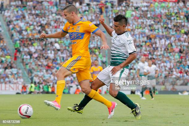 Jesus Dueñas of Tigres and Osvlado Martinez of Santos fight for the ball during the 2nd round match between Santos Laguna and Tigres UANL as part of...