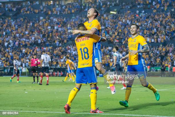Jesus Duenas of Tigres celebrates with teammates Ismael Sosa and Andre Gignac after scoring his team's second goal during the quarter finals first...