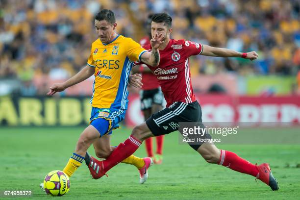 Jesus Duenas of Tigres fights for the ball with Guido Rodriguez of Tijuana during the 16th round match between Tigres UANL and Tijuana as part of the...