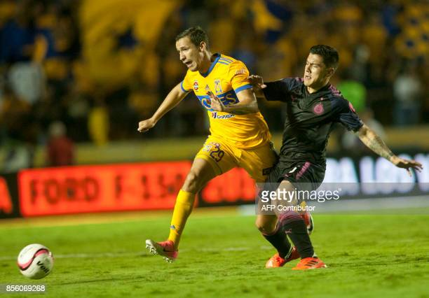 Jesus Duenas of Tigres is marked by Michael Perez of Chivas during their Mexican Apertura football tournament match at the Universitario stadium in...
