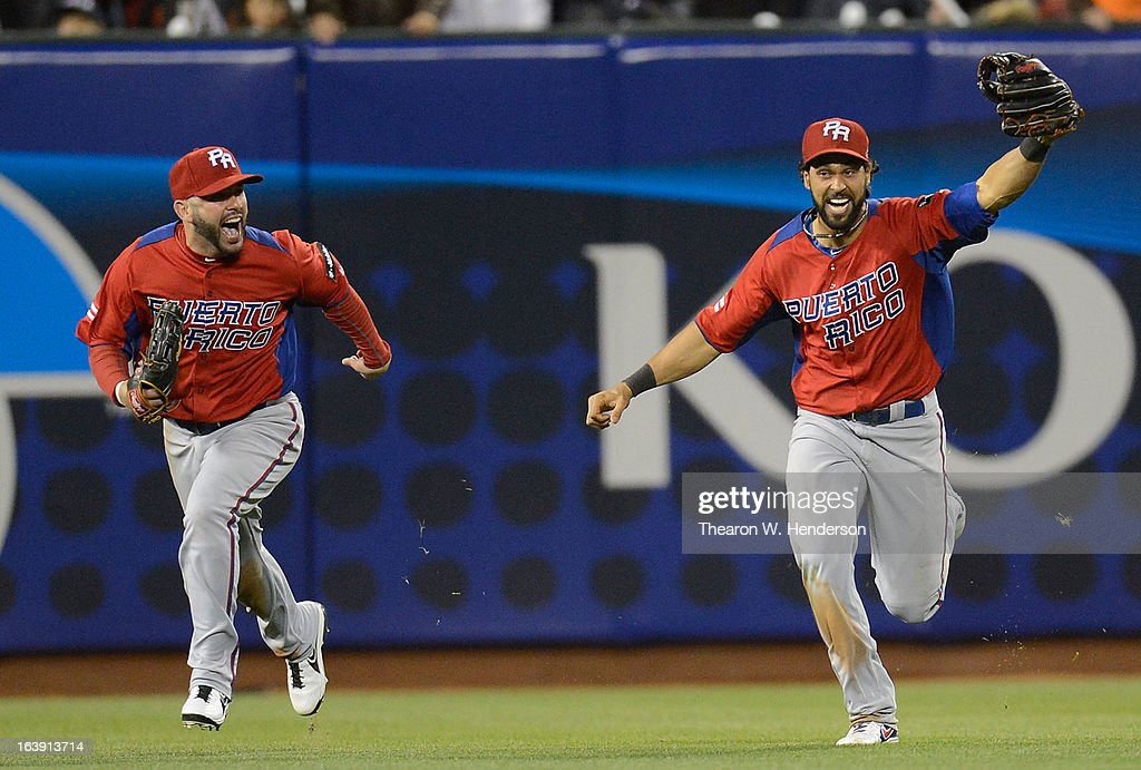 Jesus Feliciano #13 (L) and Angel Pagan #16 (R) of Team Puerto Rico celebrate defeating Team Japan 3 to 1 in the World Baseball Classic Semifinals at AT&T Park on March 17, 2013 in San Francisco, California.