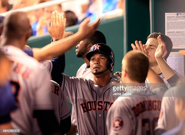 Jesus Guzman of the Houston Astros is congratulated by teammates in the dugout after scoring during the 8th inning of the game against the Kansas...