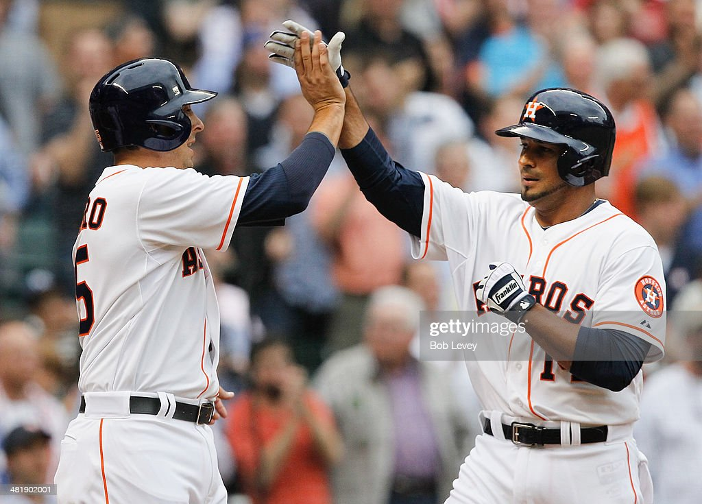 Jesus Guzman #14 of the Houston Astros receives a high-five from Jason Castro #15 after hitting a home run in the first inning against the New York Yankees at Minute Maid Park on April 1, 2014 in Houston, Texas.