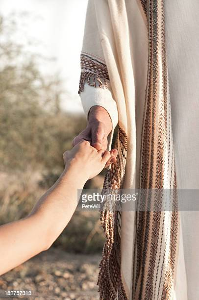 Jesus holding a persons hand outdoors