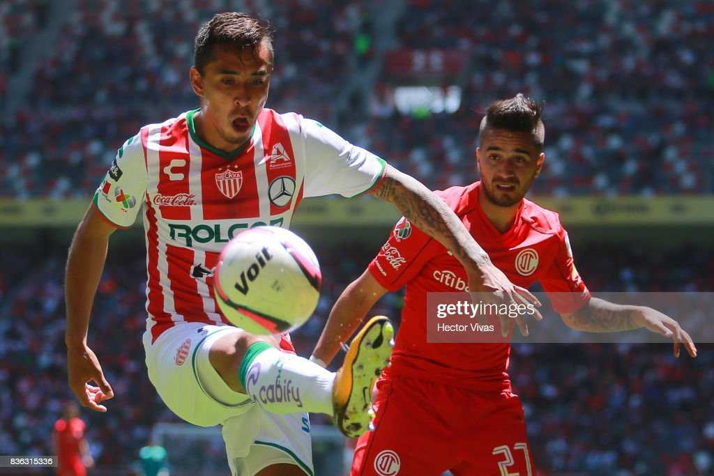 Jesus Isijara of Necaxa struggles for the ball with Rodrigo Gomez of Toluca during the fifth round match between Toluca and Necaxa as part of the Torneo Apertura 2017 Liga MX at Nemesio Diez Stadium on August 20, 2017 in Toluca, Mexico.