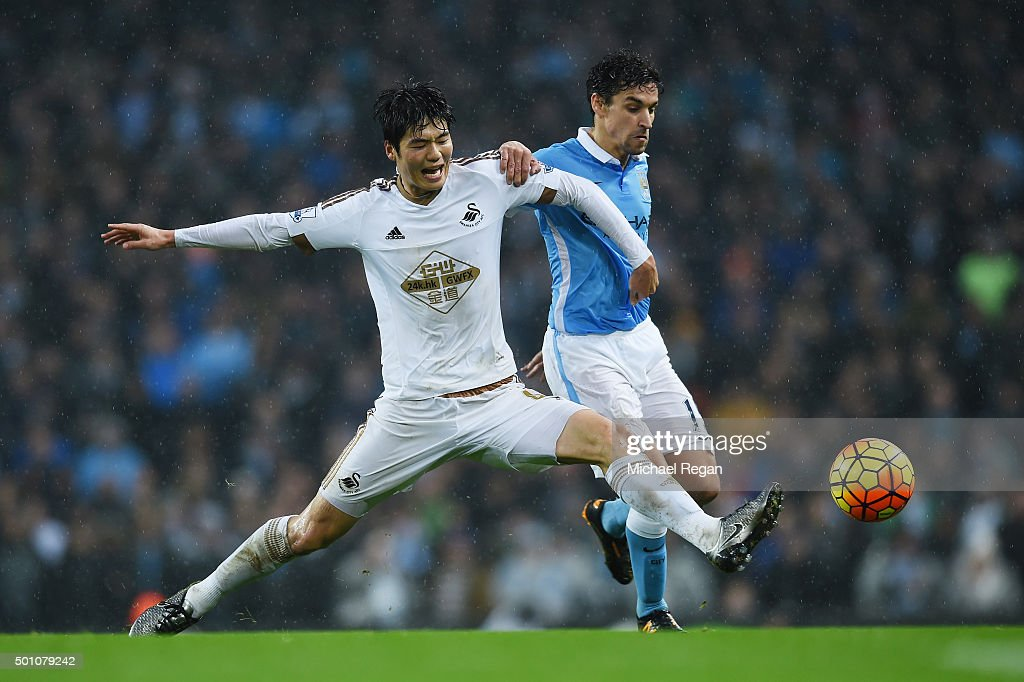 Jesus Navas of Manchester City and Ki Sung-Yeung of Swansea City compete for the ball during the Barclays Premier League match between Manchester City and Swansea City at Etihad Stadium on December 12, 2015 in Manchester, United Kingdom.