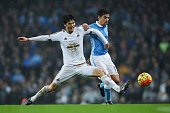 Jesus Navas of Manchester City and Ki SungYeung of Swansea City compete for the ball during the Barclays Premier League match between Manchester City...