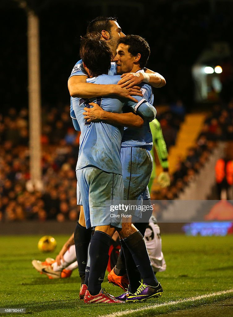 Jesus Navas of Manchester City celebrates scoring their third goal with team mates during the Barclays Premier League match between Fulham and Manchester City at Craven Cottage on December 21, 2013 in London, England.
