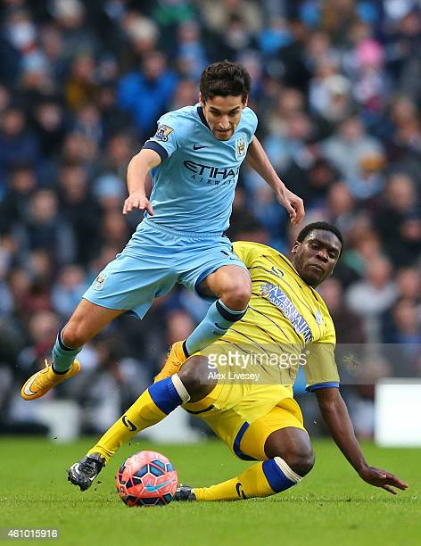 Jesus Navas of Manchester City is tackled by Jeremy Helan of Sheffield Wednesday during the FA Cup Third Round match between Manchester City and...