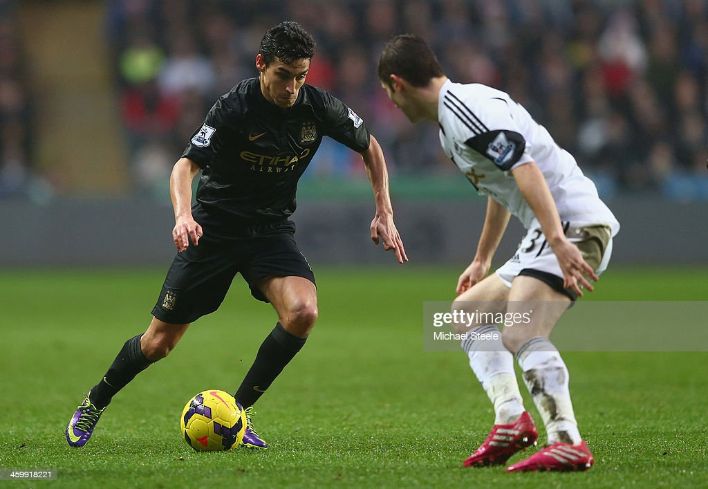 Jesus Navas (L) of Manchester City runs at Ben Davies (R) of Swansea City during the Barclays Premier League match between Swansea City and Manchester City at the Liberty Stadium on January 1, 2014 in Swansea, Wales.