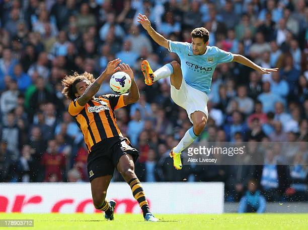 Jesus Navas of Manchester City tackles Tom Huddlestone of Hull City during the Barclays Premier League match between Manchester City and Hull City at...
