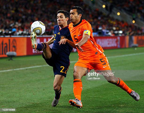 Jesus Navas of Spain and Giovanni Van Bronckhorst of the Netherlands battle for the ball during the 2010 FIFA World Cup South Africa Final match...