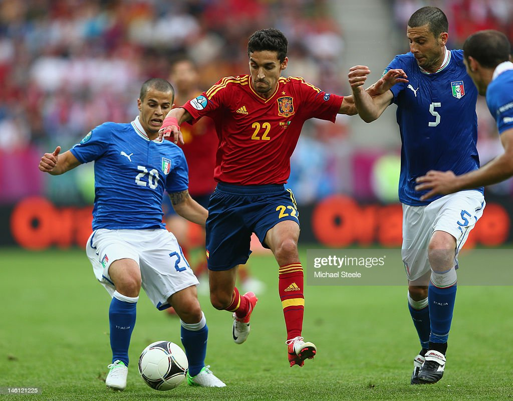 Jesus Navas of Spain cuts between Sebastian Giovinco and Thiago Motta of Italy during the UEFA EURO 2012 group C match between Spain and Italy at The...