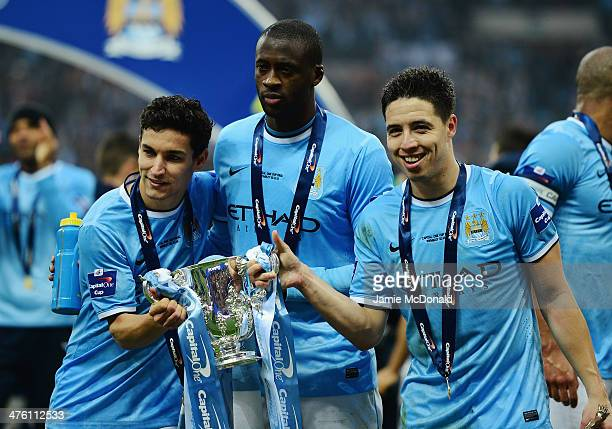 Jesus Navas Yaya Toure and Samir Nasri of Manchester City pose with the trophy after the Capital One Cup Final between Manchester City and Sunderland...