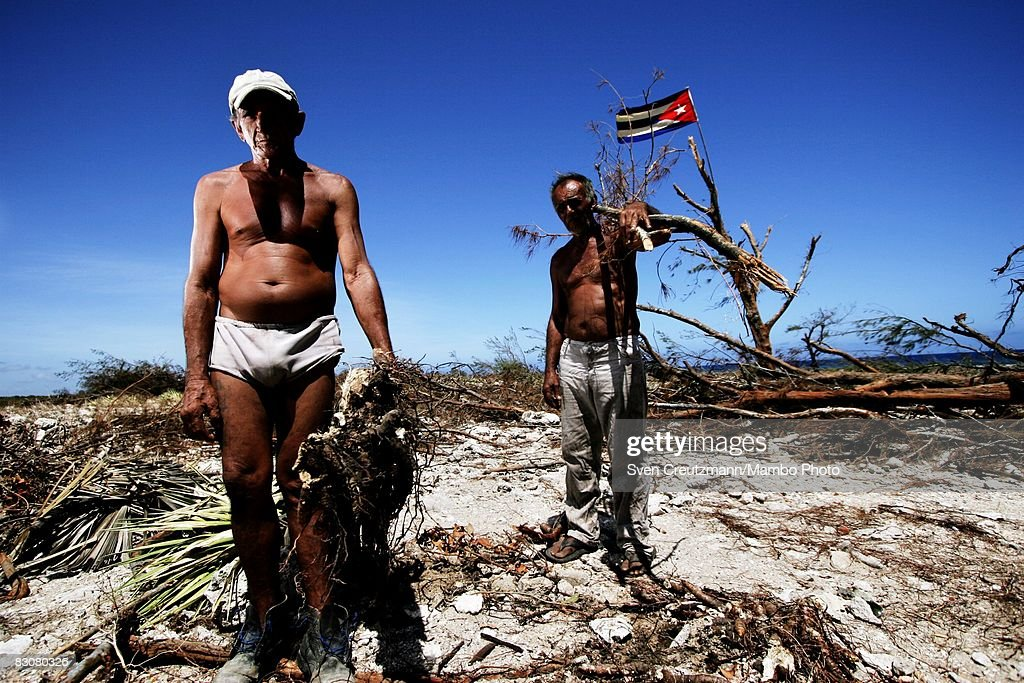 Jesus Ramirez Tejeda and Ramon Aguilera Catala pause from clearing debris on a farm destroyed as Hurricane Ike tore through a week earlier September...