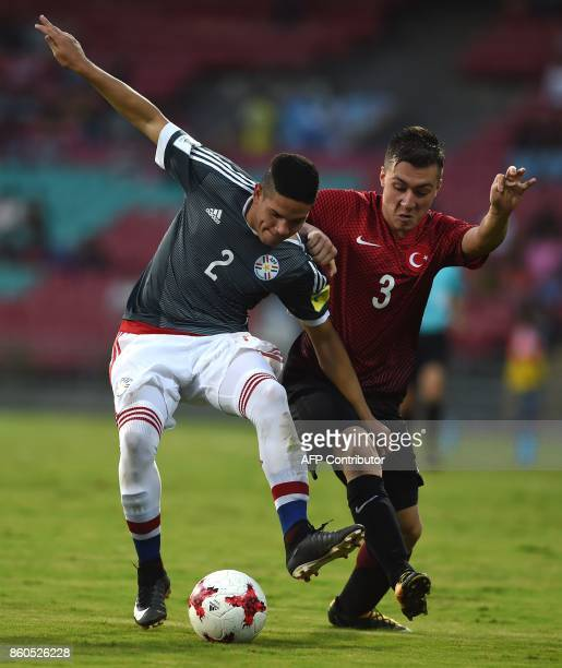Jesus Rolon of Paraguay and Melih Gokcimen of Turkey vie for the ball during the group stage football match between Turkey and Paraguay in the FIFA...