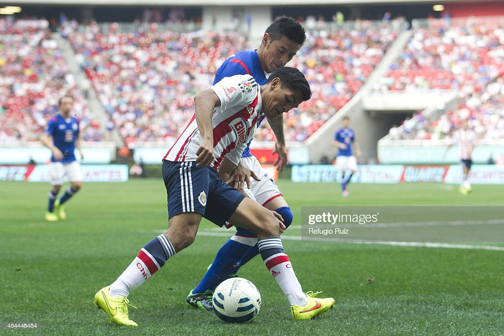 Jesus Sanchez of Chivas fights for the ball with Rogelio Chavez of Cruz Azul during a match between Chivas and Cruz Azul a as part of Apertura 2014 Liga MX at Omnilife Stadium on August 31, 2014 in Guadalajara, Mexico.
