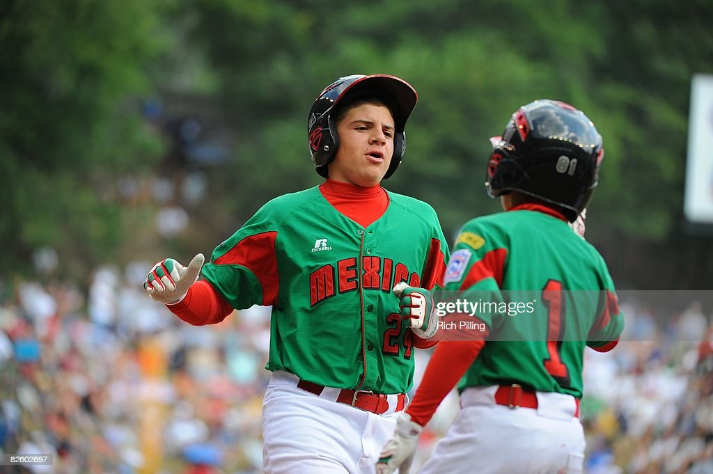 Jesus Sauceda #24 of the Matamoros Team is greeted by Octavio Salinas #1 after hitting a home run during the World Series Championship game against the Waipio Little League team at Lamade Stadium in Williamsport, Pennsylvania on August 24, 2008. The Waipio team defeated the Matamoros team 12-3.