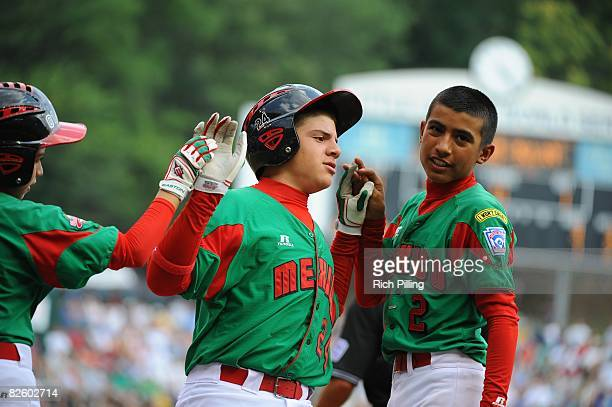 Jesus Sauceda of the Matamoros Team is greeted by Octavio Salinas and Tomas Castillo after hitting a home run during the World Series Championship...