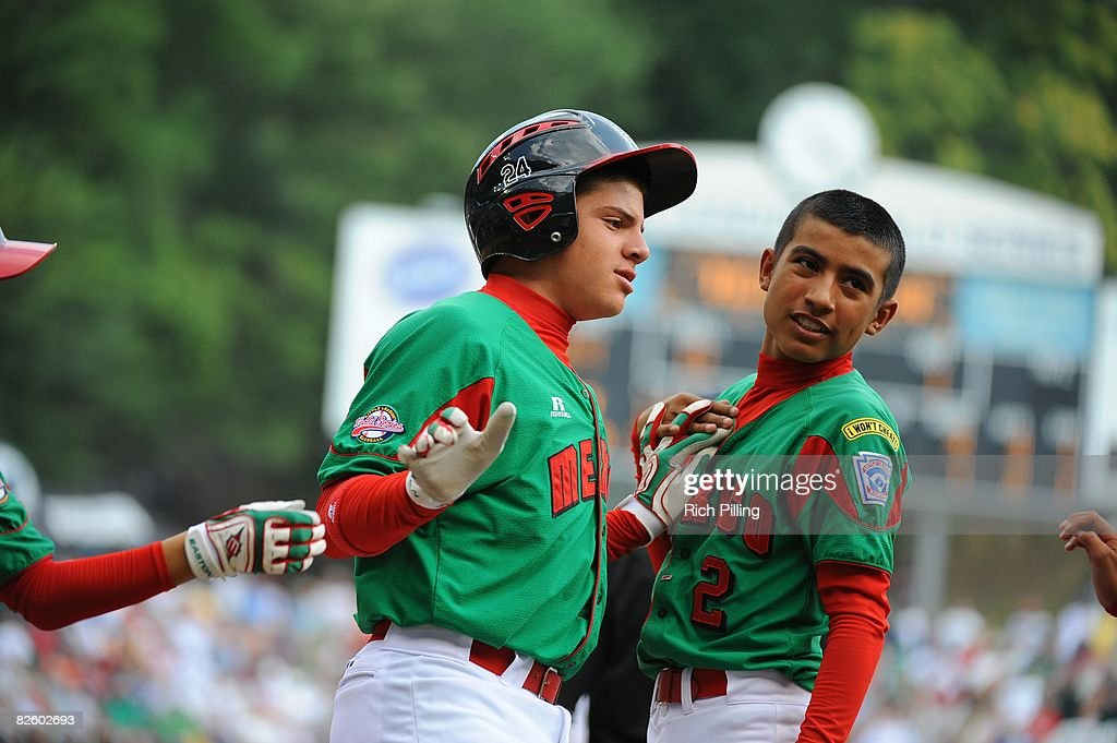 Jesus Sauceda #24 of the Matamoros Team is greeted by Tomas Castillo #2 after hitting a home run during the World Series Championship game against the Waipio Little League team at Lamade Stadium in Williamsport, Pennsylvania on August 24, 2008. The Waipio team defeated the Matamoros team 12-3.