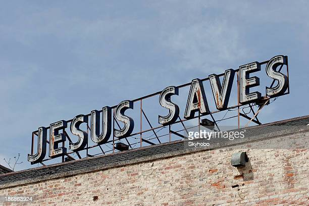 Jesus Saves light-up sign in sky over an old brick building