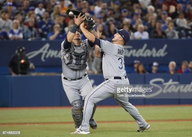 Jesus Sucre of the Tampa Bay Rays catches a pop up as he collides with Matt Andriese in the fourth inning during MLB game action against the Toronto...