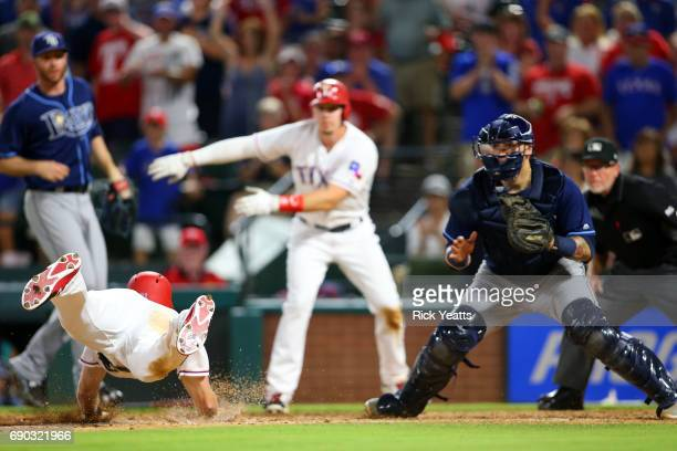 Jesus Sucre of the Tampa Bay Rays looks on as Joey Gallo of the Texas Rangers motions to Ryan Rua sliding in to home in the ninth inning at Globe...