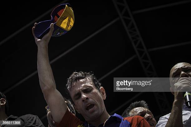 Jesus Torrealba secretarygeneral of the opposition coalition right addresses supporters while Henrique Capriles opposition leader and twotime...